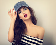 Beautiful young make-up model holding blue cap with long ha Royalty Free Stock Images