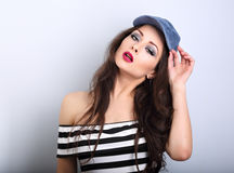 Beautiful young make-up model holding fashion blue cap and Royalty Free Stock Image