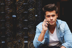 Beautiful sexy young man with a sweet smile, talking on the phone sitting on the steps Stock Image