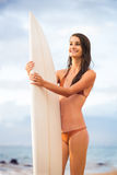 Beautiful sexy young surfer girl in bikini on the beach at sunse Royalty Free Stock Images