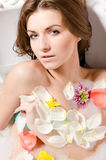 Beautiful sexy young woman in bath with flower petals. Beautiful sexy girl in bath with flower petals closeup face portrait looking at camera Stock Photos