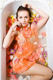 Beautiful young woman in bath with flower petals Royalty Free Stock Photography