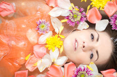 Beautiful young female in bath with flower petals Royalty Free Stock Image