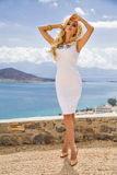 Beautiful sexy young woman from blonde curly long hair is standing in the short white challenging sexy expensive dress at the salt. Beauties blonde hair young Royalty Free Stock Image