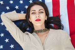 Beautiful sexy young woman with classic dress lying down on american flag in the park. fashion model holding us smiling and lookin Royalty Free Stock Photography