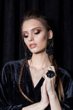 Beautiful young woman with dark hair braided with bright makeup and fashion bizhuterieyker earrings and ring, fashion jewelry stock photography