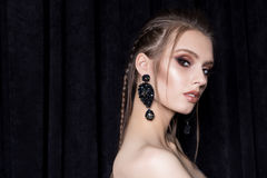 Beautiful young woman with dark hair braided with bright makeup and fashion bizhuterieyker earrings and ring, fashion jewelry royalty free stock photography