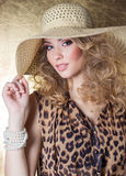 Beautiful young woman in dress leopard bright makeup in the Studio on a gold background in the hat royalty free stock image