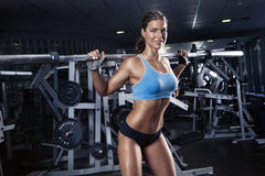 Beautiful sexy young woman in gym. Beautiful sporty sexy woman doing squat workout in gym Royalty Free Stock Images