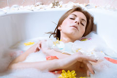 Beautiful sexy young woman having bath with flower petals. Spa body care for sensual relaxation: picture of beautiful sexy young woman pinup girl having fun Stock Photography