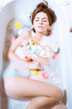 Beautiful sexy young woman having bath with flower petals. Spa body care for sensual relaxation: picture of beautiful sexy young woman pinup girl having fun Royalty Free Stock Images