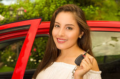 Beautiful sexy young woman holding her keys and smiling and a red car behind Royalty Free Stock Photography