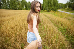 Beautiful sexy young woman holds the hand of a man in a wheat fi Stock Photos