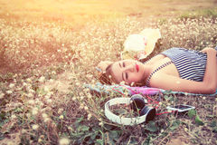 Beautiful sexy young woman lying nearing headphone in the flower Royalty Free Stock Photography