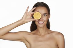 Beautiful sexy young woman with perfect healthy skin and long brown hair day makeup bare shoulders holding orange lemon grapefruit Royalty Free Stock Photo