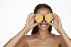 Beautiful sexy young woman with perfect healthy skin and long brown hair day makeup bare shoulders holding orange lemon grapefruit Stock Image