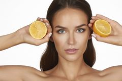 Beautiful sexy young woman with perfect healthy skin and long brown hair day makeup bare shoulders holding orange lemon grapefruit Royalty Free Stock Photography