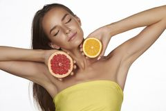 Beautiful young woman with perfect healthy skin and long brown hair day makeup bare shoulders holding orange lemon grapefruit Stock Photo
