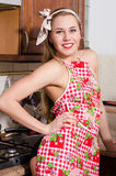 Beautiful young woman pinup girl in apron laughing in kitchen portrait picture Stock Image