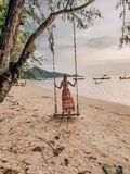 Beautiful, sexy, young woman posing on the beach in Thailand, Phangan island wearing red bikiniWoman standing on a swing on the be stock photo
