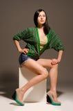 Beautiful sexy young woman posing sitting. Studio Stock Image