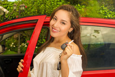 Beautiful sexy young woman in red car holding keys and smiling Royalty Free Stock Photo