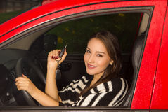 Beautiful young woman in red car holding keys and smiling Royalty Free Stock Images