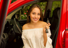 Beautiful young woman in red car holding keys and smiling Stock Photos