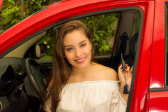 Beautiful young woman in red car holding keys and smiling Stock Images
