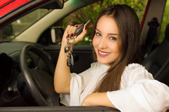 Beautiful young woman in red car holding keys and smiling Stock Image