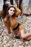 Beautiful sexy young woman sit floor with lot of golden sequins. Glamour fashion model  perfume wear style dress brunette long hair evening makeup celebrate Stock Photography