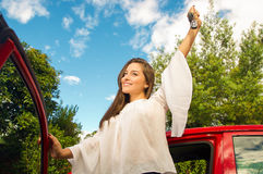 Beautiful sexy young woman staring up while she hold her keys and smiling near to her red car Royalty Free Stock Image