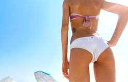 Beautiful sexy young woman walks on the beach. Woman buttocks slim figure on the beach with sky background. Happy woman enjoys summer vacation and goes to swim royalty free stock photography