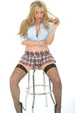 Beautiful Sexy Young Woman Wearing A Short Mini Skirt Blue Shirt. Sexy young alluring flirtatious young woman, sitting perched on bar stool playing cheekily with Royalty Free Stock Photography