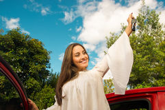 Beautiful young woman wearing a white blouse coming out of her red car and holding a keys while she is smiling Royalty Free Stock Images