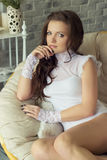 Beautiful sexy young woman in a white bodysuit sitting near the window in a comfortable chair Royalty Free Stock Photos