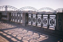 Railings of the bridge in Riga. Beautiful shadow from the bridge on the waterfront Royalty Free Stock Image