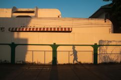 Beautiful shadow of women runner on cream wall background. Sunset light shines down around the wall and house. Running isolate stock images