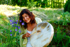Beautiful shamanic girl with shaman frame drum on background with leaves and flowers. Stock Photography