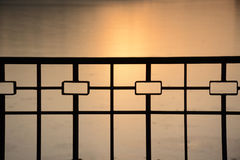Beautiful shape of metallic fence on the sunset background. Forged fence at setting sun rays background Royalty Free Stock Image