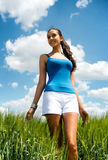 Beautiful shapely young woman in a grassy field. Low angle view of a beautiful tanned shapely young woman in shorts, standing in a field of long green grass Stock Photos
