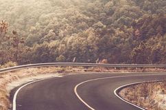 Beautiful sharp curve of local Road in big forest. Stock Photo