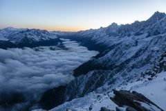 Beautiful sharp peaks start to shine as the sun rises in the French Alps. A view of the valley above the clouds with beautiful sharp peaks start to shine as the Royalty Free Stock Image