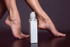 Beautiful shaved perfect female legs and foot cream. Studio shot Stock Photos