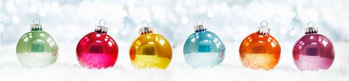 Beautiful shiny Christmas ball banner. Arranged in a row on fresh white winter snow with a backdrop of sparkling lights