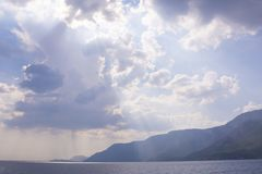 Beautiful shiny clouds above Aegean Islands on sea and mountains background, Turkey. Beautiful shiny clouds with sun rays above Aegean Islands on sea and royalty free stock photography