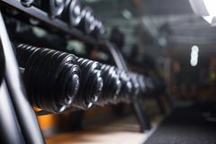 A set of barbells on a gym background. Black metal heavy dumbbells on shells. Bodybuilding, physical training concept. A beautiful, shiny set of black, metal Royalty Free Stock Images
