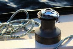 Windlass on a board of a yacht with water background. Beautiful shiny windlass on a board of a yacht or motor boat with a blue mooring cable rope on blue water Stock Photos