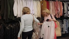 Beautiful shopaholic women buying clothes in store stock video footage