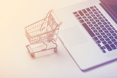 Beautiful shopping cart and cool laptop on the wonderful pink ba Stock Photography